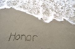 Honor in the sand. Honor written in the sand with a wave Stock Images