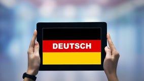 Honor som håller pekfinger med tyskt ord mot nationell flagga, onlineapp stock video