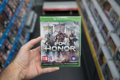 For Honor videogame on XBOX One. Bratislava, Slovakia, circa april 2017: Man holding For Honor videogame on Microsoft XBOX One console in store Royalty Free Stock Photo