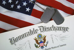 Military  dog tags on honorable discharge document. Military discharge paper and dog tags on an American flag Stock Images