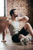 Honored sip. Confident muscled young man wearing sport wear and drinking water while sitting on the floor in loft interior Stock Photo