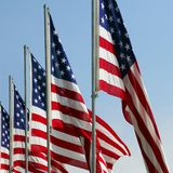 Honoring Fallen Heroes - American Flags On Memorial Day. Flags fly proudly on a clear blue sky day. It's Memorial day and the fallen are honored at a national Stock Photography