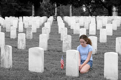 Honoring The Fallen SC. A young girl in a military cemetary honoring a fallen soldier  - selective colorization Royalty Free Stock Image