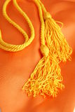 Honors Graduation Cord. Gold honors graduation cord with tassels on orange silk honors stole royalty free stock photo