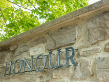 Honour. The word honour in metal letters on a stone wall with green treed background Stock Photo