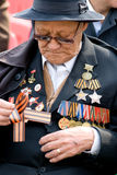 Honourable veteran. ULAN-UDE, RUSSIA - MAY 9: An elderly veteran wearing a lot of decorations attaches St. George's ribbon - symbol of victory at the parade on stock photography