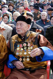 Honourable veteran. ULAN-UDE, RUSSIA - MAY 9: An elderly veteran in Buryat national clothes wearing a lot of decorations watches the parade on annual Victory Day royalty free stock photography