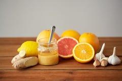 Honung, citrusfrukter, ingefära och vitlök på trä Arkivbild