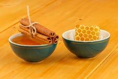 Honung, honungskaka och kanel i bunkar fotografering för bildbyråer