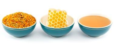 Honung, honungskaka och pollen i bunkar arkivbild