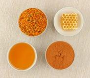 Honung, honungskaka, pollen och kanel i bunkar royaltyfri fotografi