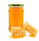 Honung i en krus och en honungskaka Arkivfoto
