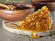 Honung i en träbunke och en honungskaka arkivfoton