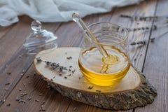 Honung i exponeringsglaskrus med honungskopan på lantlig träbakgrund royaltyfria bilder