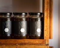 Honung i exponeringsglaskrus med till salu svarta lock shoppar på hyllor som göras av gamla bibikupor arkivbild