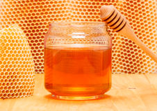 Honung i krus med skopan på honungskakabakgrund Royaltyfria Bilder