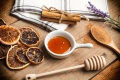 Honung, kanelbruna rullar och torkade apelsiner Royaltyfria Foton