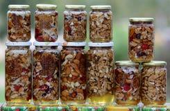 Honung med muttrar och frukter arkivbilder