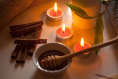 Honung och aromatiska stearinljus på tabellen Royaltyfria Foton