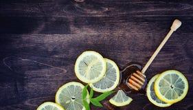 Honung och citron Honungpinne och skivor av den skivade citronen på en uppvakta arkivfoton