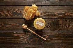 Honung och honungskaka med pinnen Arkivfoto