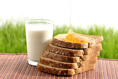 Honung och mjölkar med bröd Arkivfoto