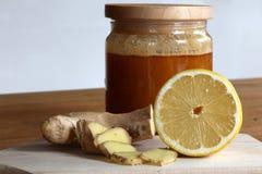 Honung, skivad ingefära och halv citron royaltyfria foton