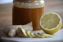 Honung, skivad ingefära och halv citron royaltyfri fotografi