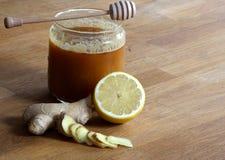 Honung, skivad ingefära och halv citron royaltyfria bilder
