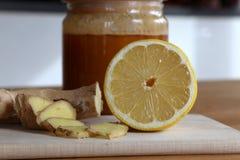 Honung, skivad ingefära och halv citron arkivfoto