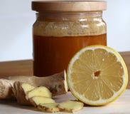 Honung, skivad ingefära och halv citron arkivfoton