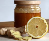 Honung, skivad ingefära och halv citron arkivbild