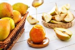 Honung som hälls på ett päron, nya päron och skivade päron Arkivfoto