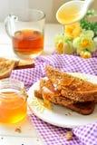 Honung som hälls på rostat bröd - frukost Arkivfoto