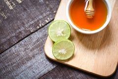 Honungcitronlimefrukt på skärbräda med honungkoppen på mörk träbakgrund royaltyfria bilder