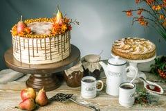 Honungkakan häller över chokladen och dekorerat med päron och havsbuckthornen på en trätabell Söt höststilleben arkivfoton