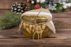 Honungkrus med muttrar i gåvan som förpackar kraft kran Julvinterram på mörk träbakgrund röda element ` S för nytt år arkivbilder