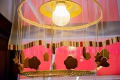 Honungpepparkaka som hänger på en rad runt om en ljus kula Arkivbilder