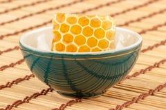 Honungskaka i bunke Arkivfoton