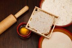 Honungskaka med den naturliga honung, mjöl, socker och kavlen Royaltyfri Foto