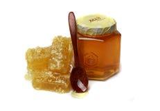 Honungskaka och banken av honung Arkivfoto