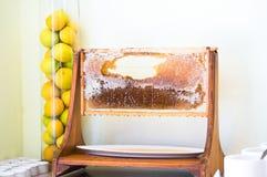 Honungskakaskärmram i restaurang och citroner åt sidan i vas för exponeringsglasrör arkivfoton