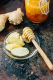 Honungskeden med biten av honung och ingefäran rotar på den glass plattan royaltyfri bild