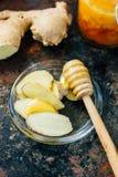 Honungskeden med biten av honung och ingefäran rotar på den glass plattan arkivbild