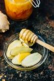 Honungskeden med biten av honung och ingefäran rotar på den glass plattan fotografering för bildbyråer