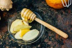 Honungskeden med biten av honung och ingefäran rotar på den glass plattan arkivfoton