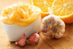 Honungvitlök och citron på den trälantliga tabellen royaltyfri fotografi