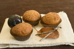 Hony cupcakes. Honey cupcakes with plum, leave and sugared vanilla sticks Royalty Free Stock Photo