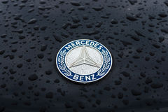 Hood emblem of Mercedes-Benz in raindrops on the dark background. Stock Photography