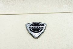 Hood emblem of sports car Volvo P1800 in raindrops on the white background. Stock Image